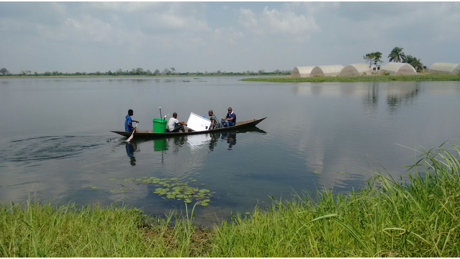 Four men and a solar pump in a boat on a lake in Ghana