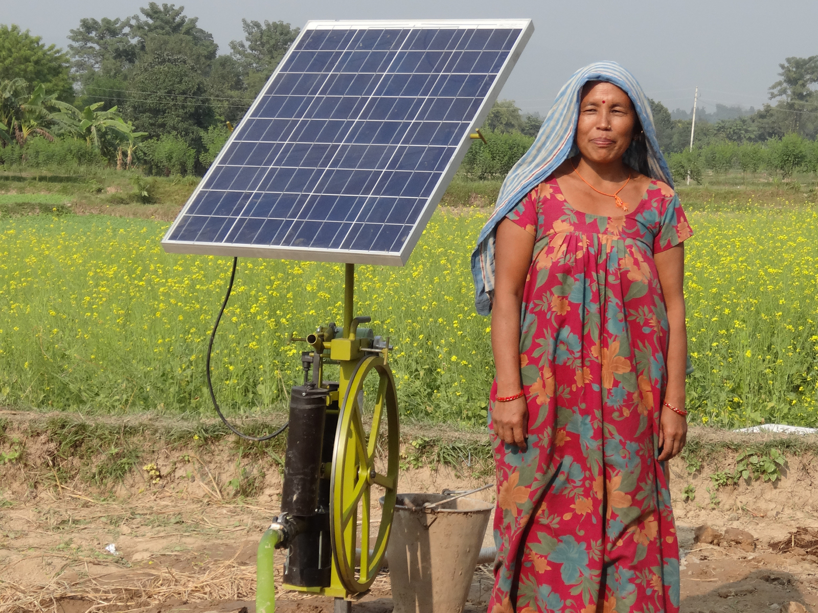 A female farmer stands next to her solar irrigation pump in a field in Nepal