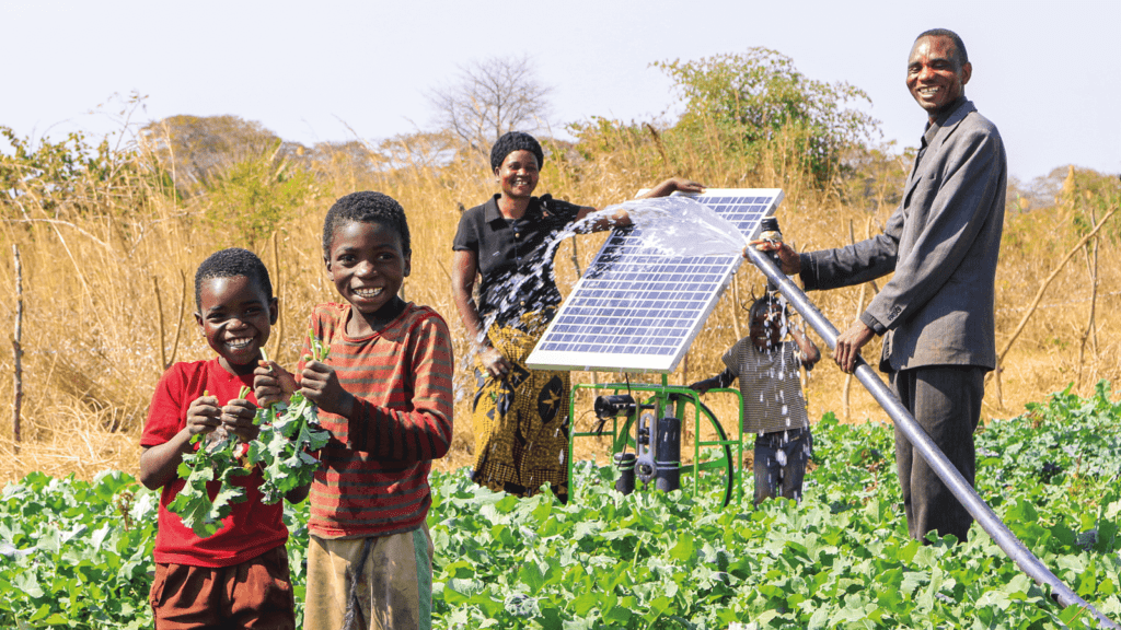 A family in Zambia standing with a Futurepump solar pump on a farm surrounded by crops