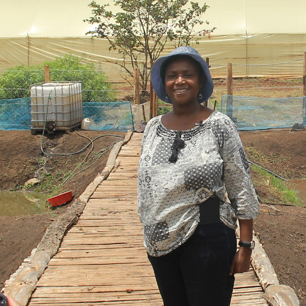 A smiling woman called Ann. She is standing on a wooden walkway on her farm. She has a hat on to protect from the bright sunlight and there is a white water storage tank behind her.